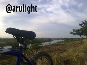 ngontel sendirian, memfoto sepeda dan sungai panjang di belakangnya